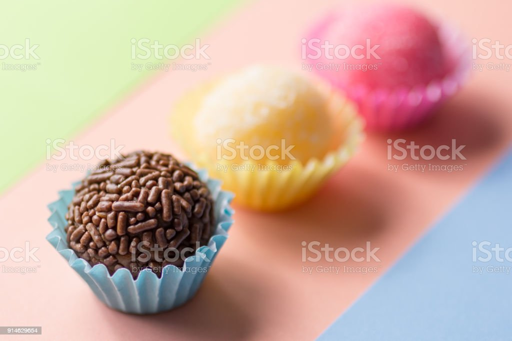 Brigadeiro Beijinho and Bicho de Pe: sweets from Brazil. Child birthday party. Candy balls in straight line. Colorful background. stock photo