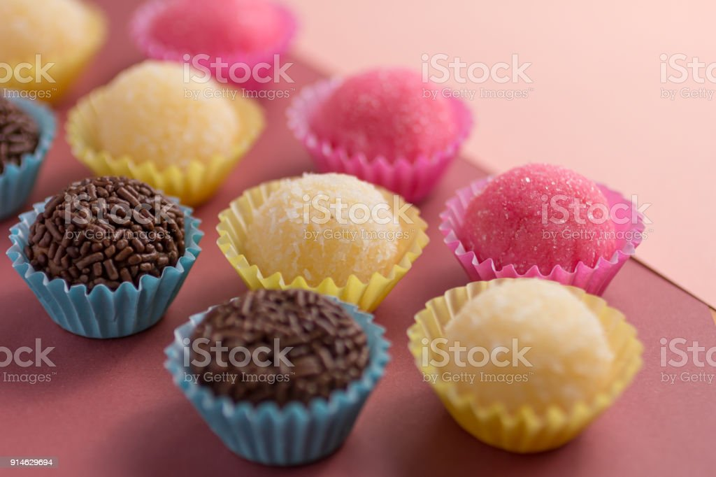 Brigadeiro, Beijinho and Bicho de Pe: sweets from Brazil. Child birthday party. Candy balls in a straight line. Colorful background. stock photo