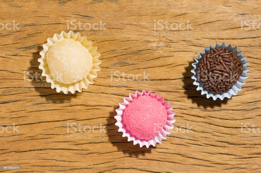 Brigadeiro Beijinho and Bicho de Pe: sweets from Brazil. Child birthday party. Overhead of candy ball on rustic wood table. stock photo