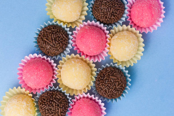 Brigadeiro Beijinho and Bicho de Pe: sweets from Brazil. Child birthday party. Overhead of candy ball on blue table. stock photo