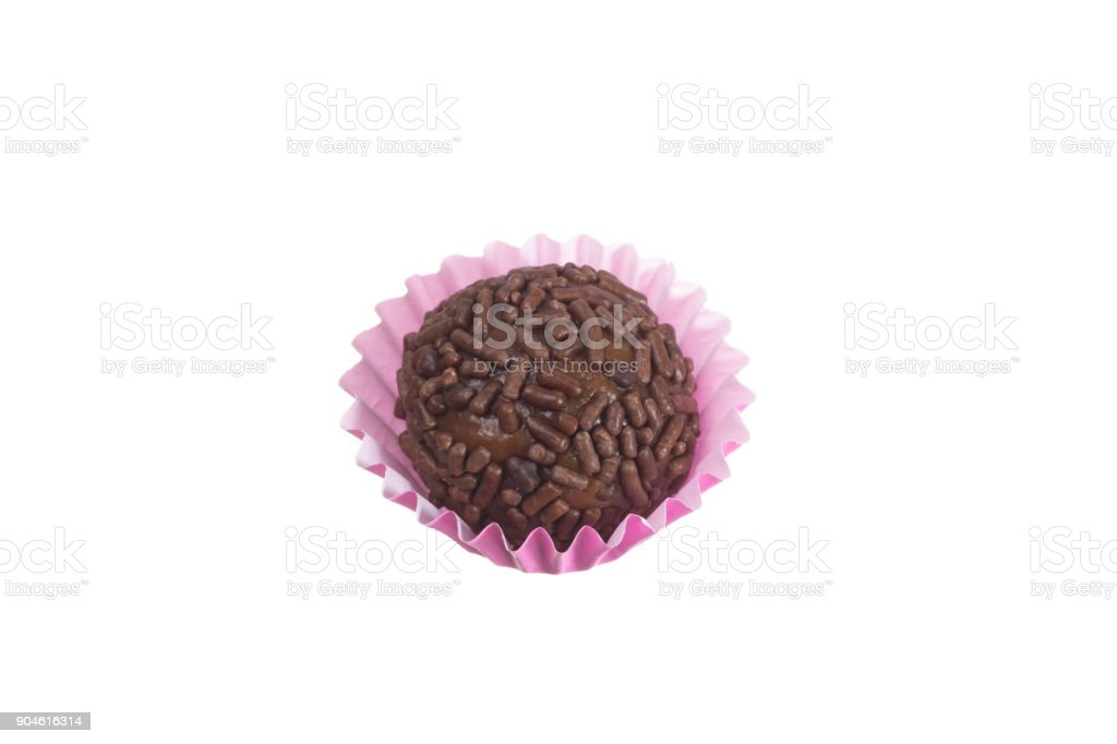 Brigadeiro is a chocolate truffle from Brazil. Cocoa and sprinkles of chocolate. Children birthday party sweet. Overhead of candy ball in white background. stock photo