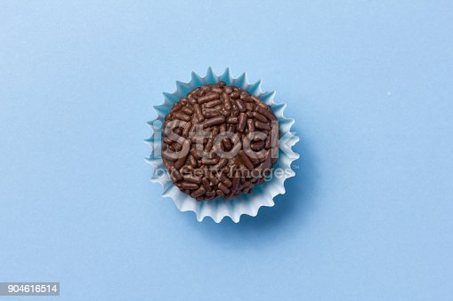 istock Brigadeiro is a chocolate truffle from Brazil. Cocoa and sprinkles of chocolate. Children birthday party sweet. Top view of candy on blue background. 904616514