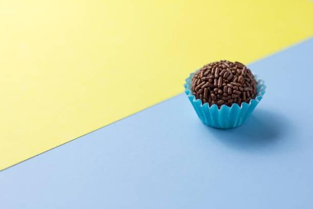 Brigadeiro é uma trufa de chocolate do Brasil. Cacau e granulado de chocolate. Doce de festa de aniversário crianças. Bola de um doce na mesa amarela e azul. - foto de acervo