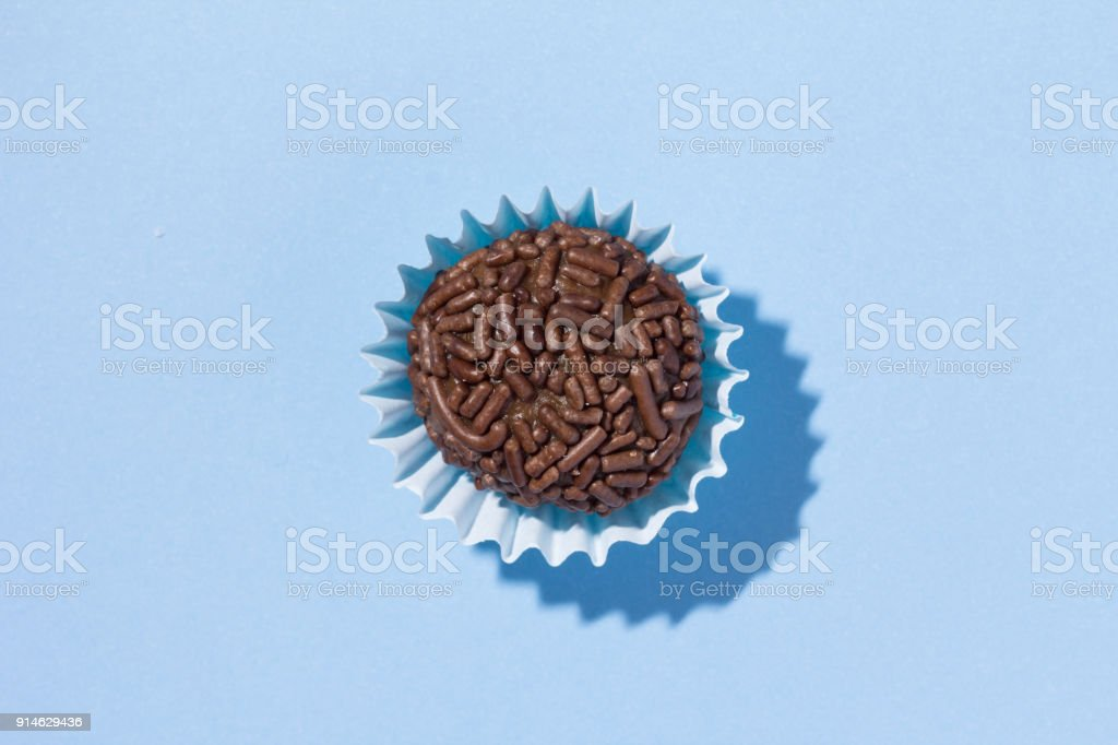 Brigadeiro is a chocolate truffle from Brazil. Cocoa and sprinkles of chocolate. Children birthday party sweet. Top view of candy on blue background. stock photo