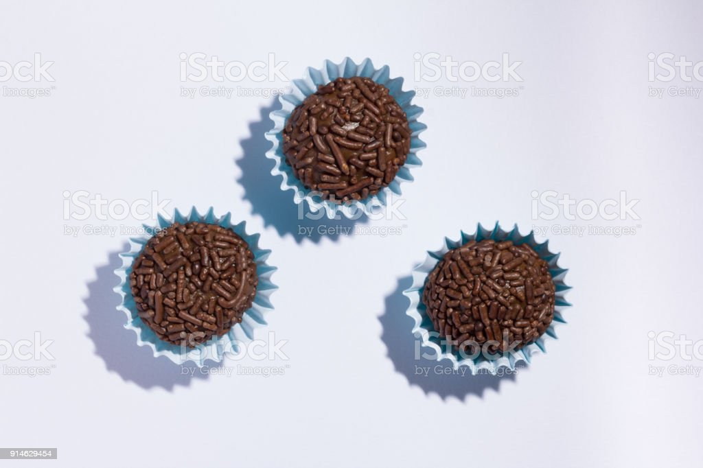 Brigadeiro is a chocolate truffle from Brazil. Cocoa and sprinkles of chocolate. Children birthday party sweet. Flat lay design of candy ball. Macro, close up. stock photo