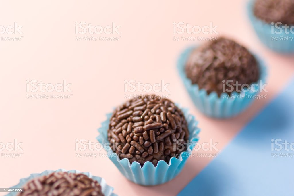 Brigadeiro is a chocolate truffle from Brazil. Cocoa and sprinkles of chocolate. Children birthday party sweet. Candy balls in a straight line. Colorful background. stock photo