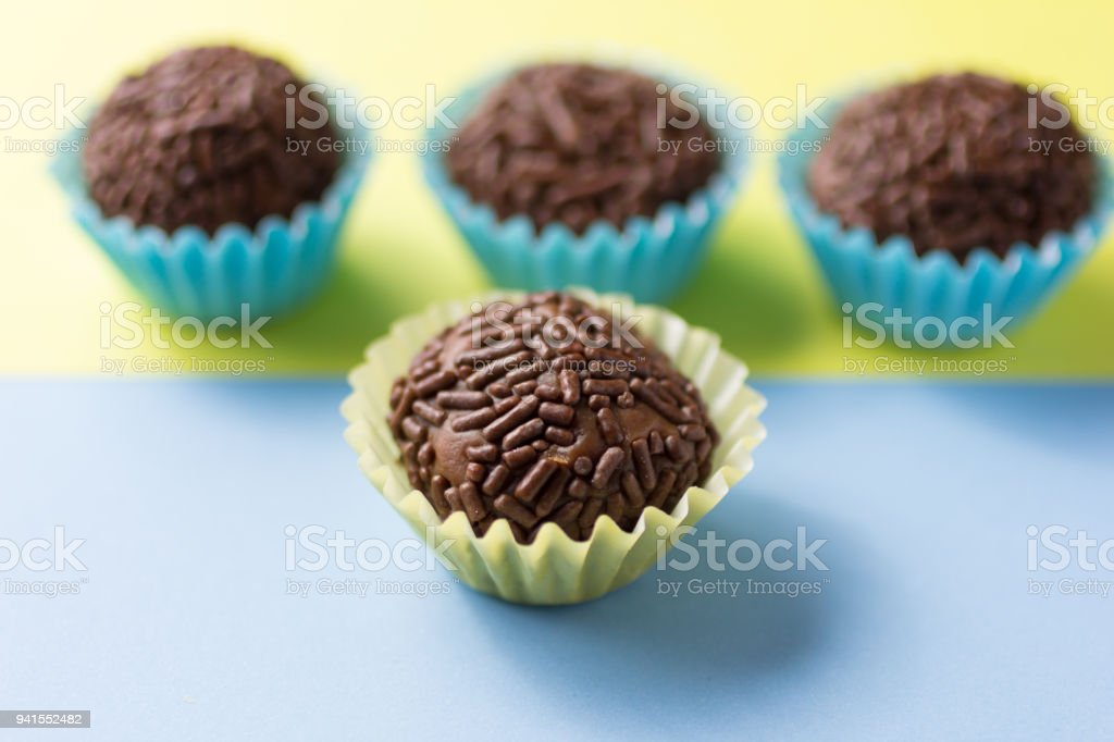 Brigadeiro is a chocolate truffle from Brazil. Cocoa and sprinkles of chocolate. Children birthday party sweet.  One candy ball in front. stock photo