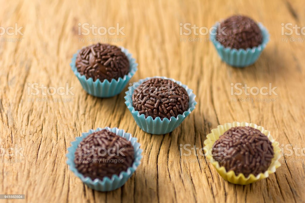 Brigadeiro is a chocolate truffle from Brazil. Cocoa and sprinkles of chocolate. Children birthday party sweet. Selective focus. Rustic wooden table. stock photo