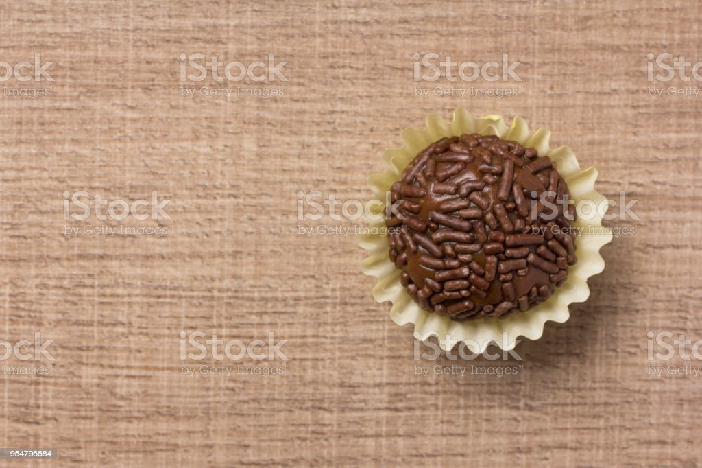Brigadeiro is a chocolate truffle from Brazil. Cocoa and sprinkles of chocolate. Children birthday party sweet. Flat lay design of candy ball over wood. stock photo