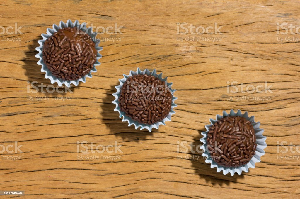 Brigadeiro is a chocolate truffle from Brazil. Cocoa and sprinkles of chocolate. Children birthday party sweet. Overhead of candy ball on rustic wood table. stock photo