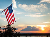 Bright american flag flying high above beautiful sunset over Mississippi river. Symbol for patriotism and peace. Background shows illuminated clouds in the sky, copyspace, no people
