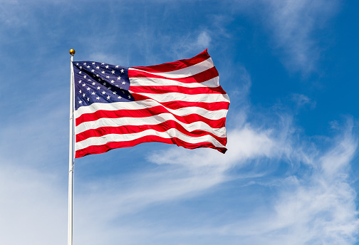 Beautiful American flag waving in the wind, with vibrant red white and blue colors against blue sky, with copy space.