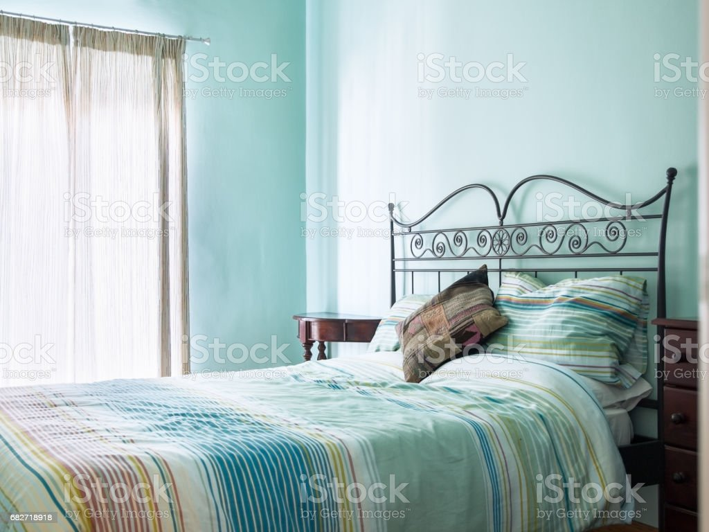 Bright and airy bedroom with rustic furniture and green / turquoise paint and soft furnishings from a bed and breakfast. stock photo