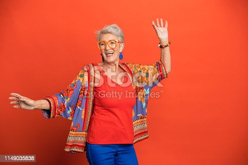 Portrait of a smiling senior woman standing in front of an orange background dressed in bright clothing with fun glasses on. Her arms are outstretched as she dances.