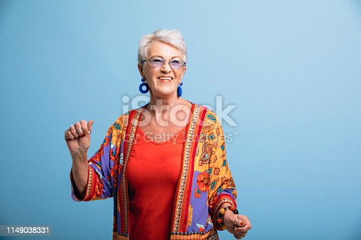 Portrait of a smiling senior woman dancing in front of a blue background. She is dressed in bright clothing and is smiling, looking away from the camera.