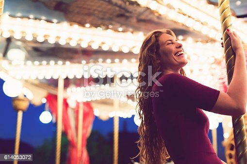 Beautiful smiling young woman on a carousel.