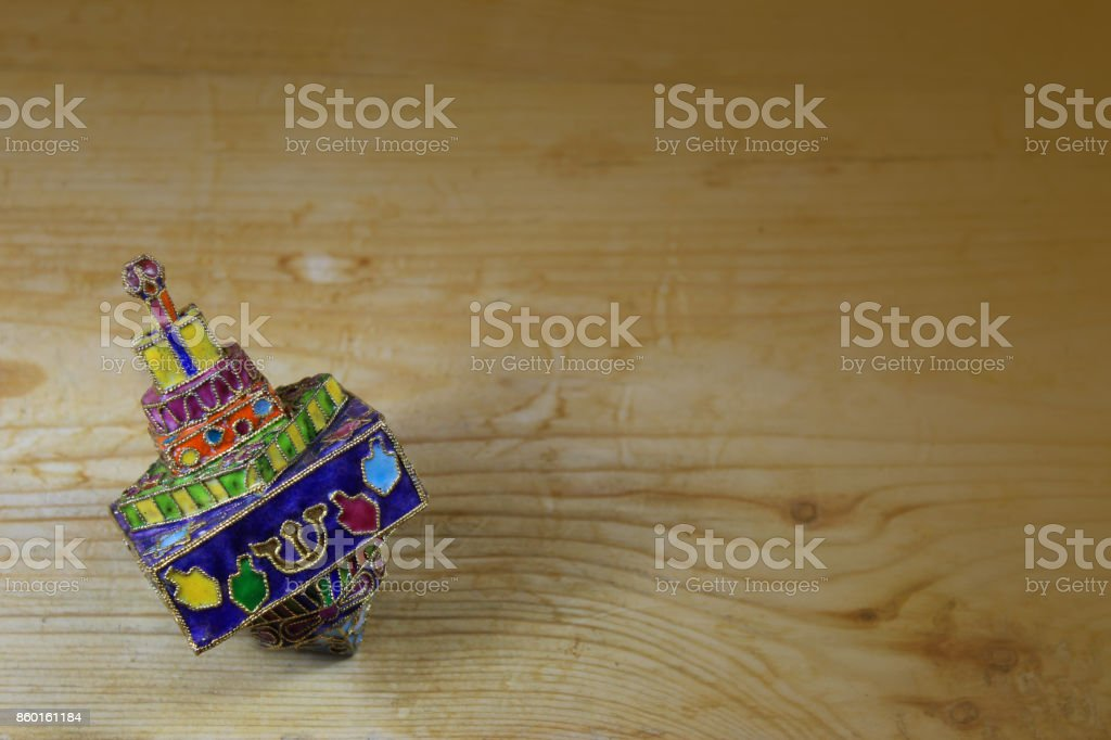 Bright and colorful enameled metal Hanukkah dreidel on a wood table stock photo