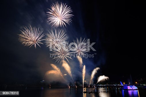 istock Bright and colorful fireworks against a black night sky.Fireworks for new year. Beautiful colorful fireworks display on the urban lake for celebration on dark night background. 908478310