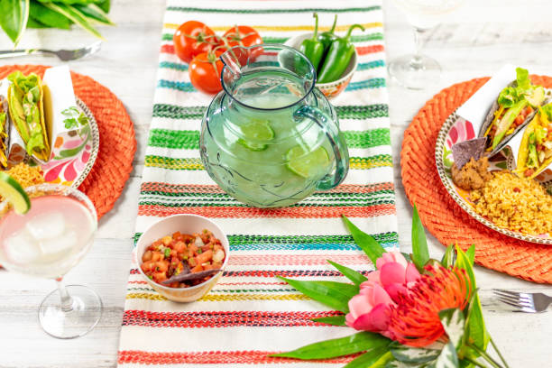 bright and colorful tabletop with pitcher of margaritas and tacos - cinco de mayo party stock photos and pictures