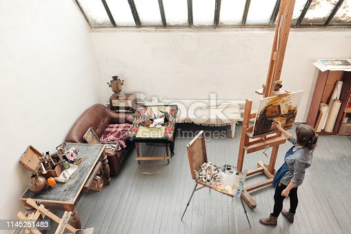 937313030 istock photo Bright art studio with a large window. Easels and canvases. Woman artist paints a picture on canvas. 1145251483