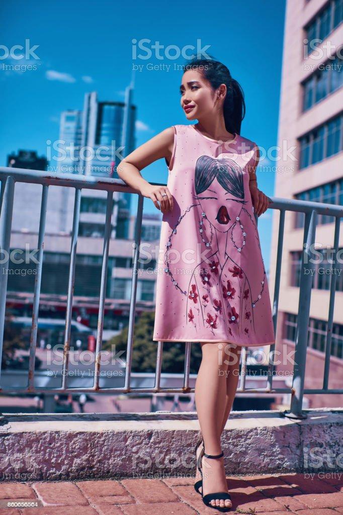 ca3e06d2594 Femme asiatique lumineuse en mode rose robe admirant la vue sur la ville  sur le balcon