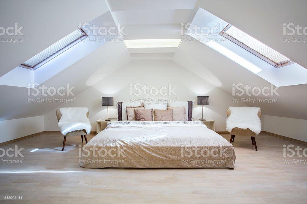 Bright attic bedroom in the apartment stock photo