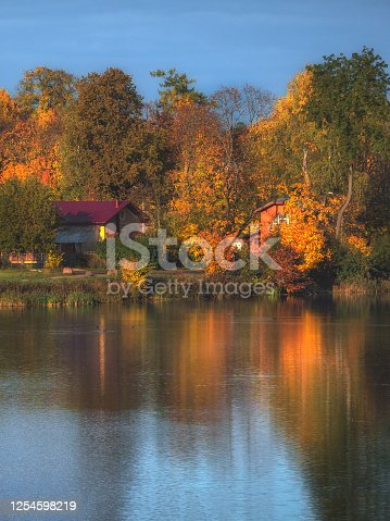 Bright autumn landscape with reflection and houses on the lake