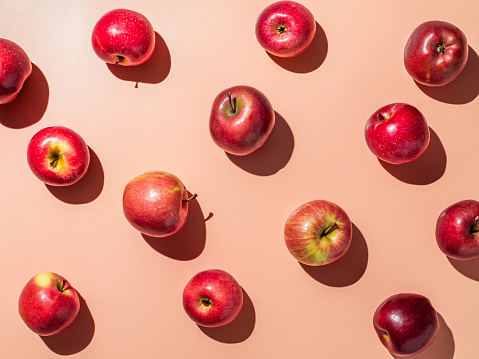 Delicious red apples on orange or coral pink background pattern. Colorful fruit frame. Flat lay or top view, Hard light. Creative concept.