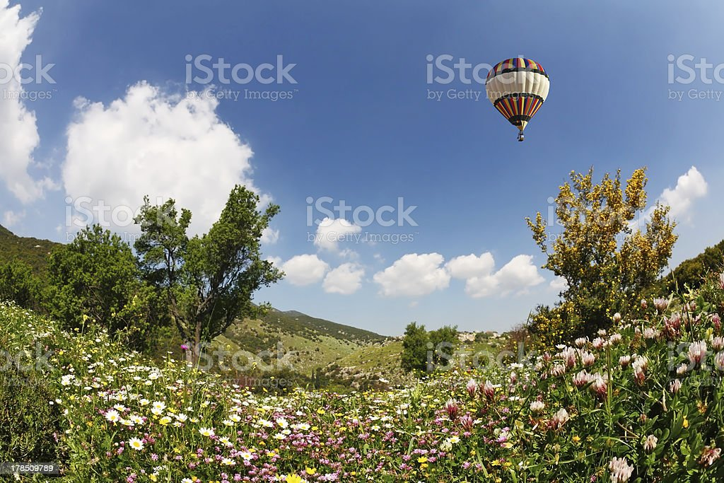 Bright balloon flying over hills royalty-free stock photo