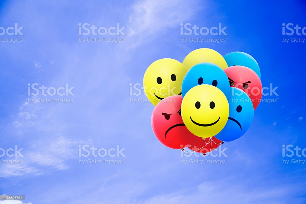Bright balloons flying in the blue sky with a smiley stock photo