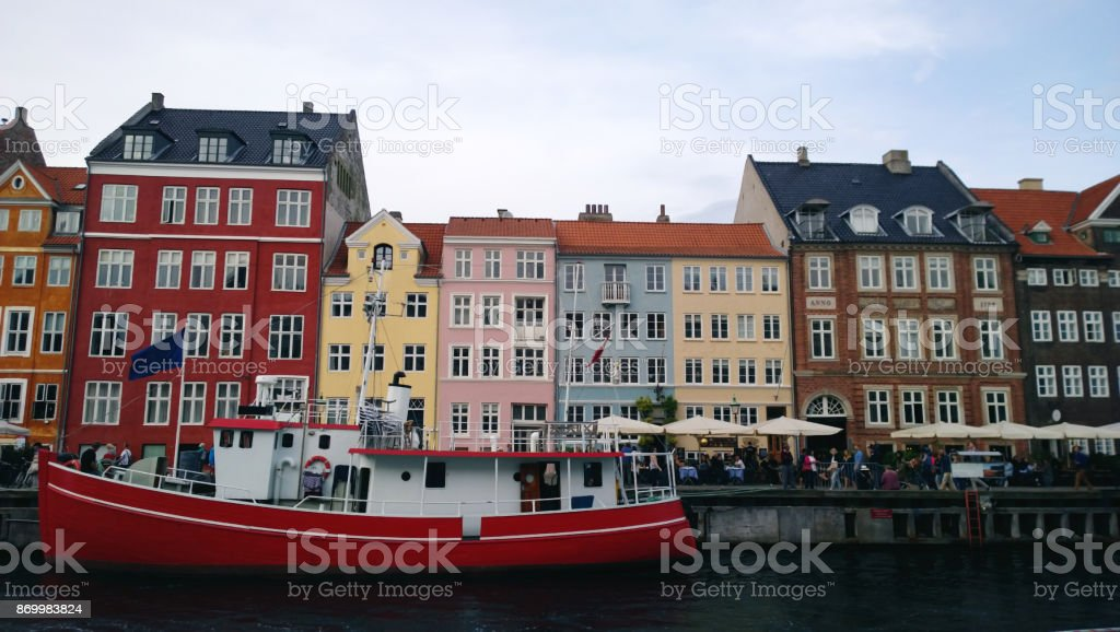 Bright beautiful facades of the buildings on the waterfront Nyhavn and the red-white ship on the water stock photo