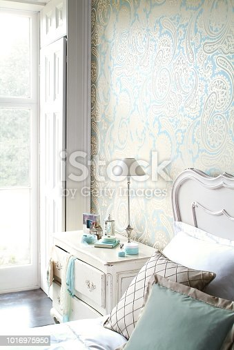Small side table with articles by the bed in bright bedroom