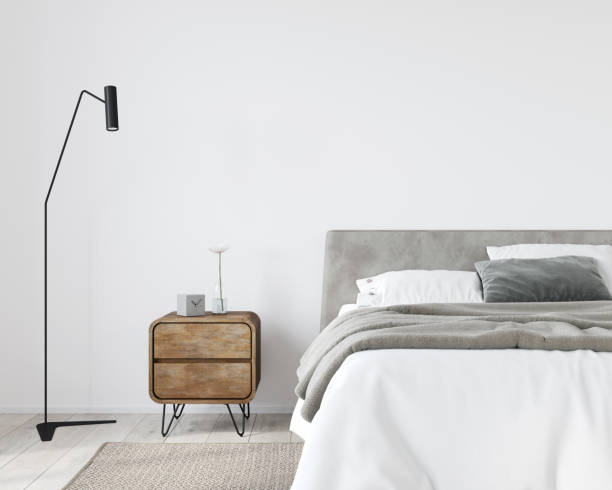 Bright bedroom with a wooden bedside table and a stylish floor lamp stock photo