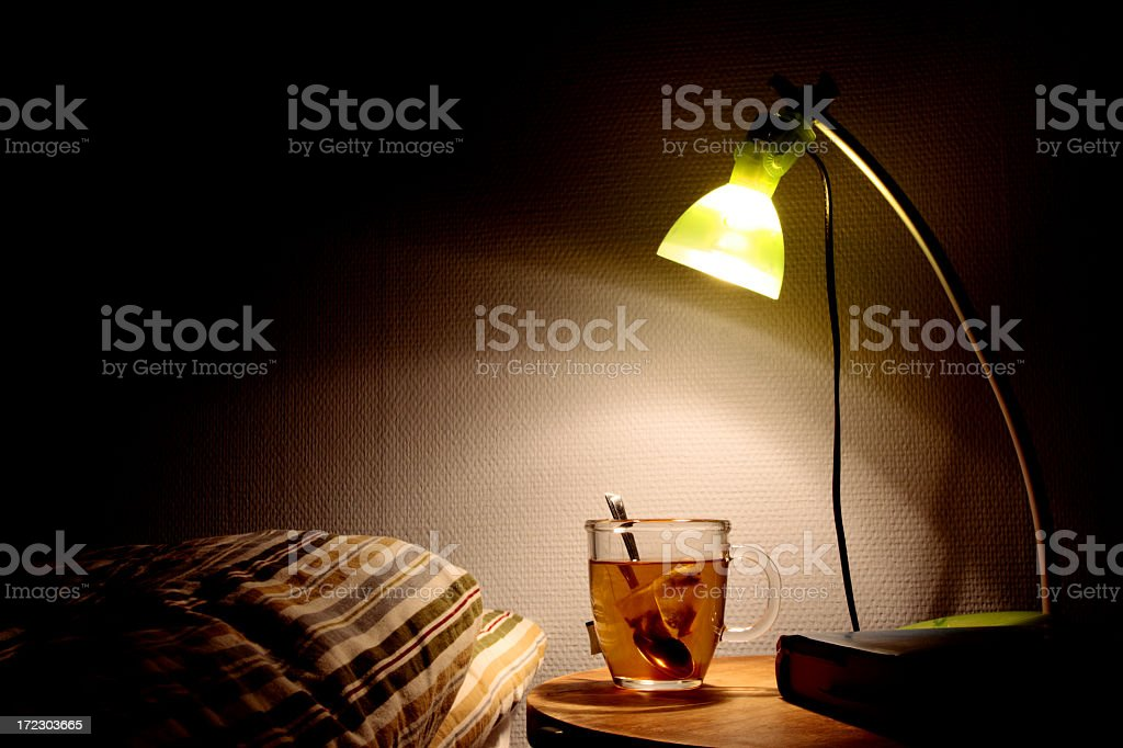 Bright bedside lamp with a clear cup of tea next to the bed stock photo