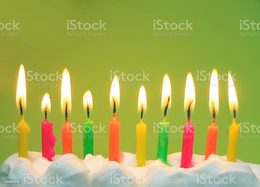 Bright birthday candles on green 10 lit brightly colored birthday candles in icing with green background Birthday Stock Photo