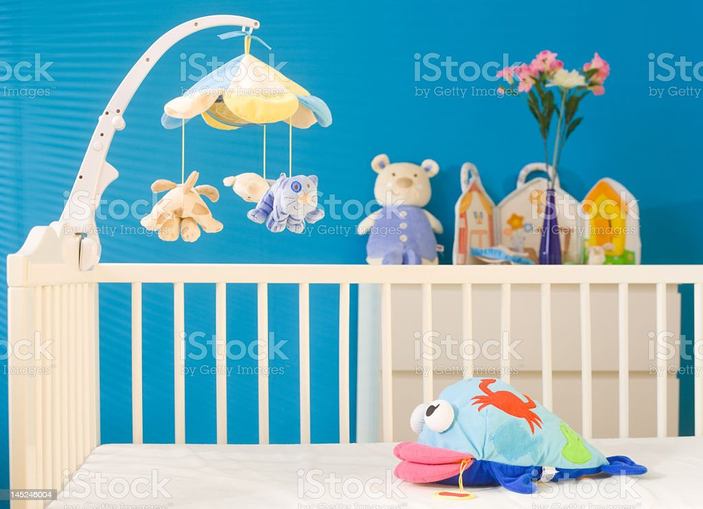 Bright blue baby's bedroom with cream cot stock photo