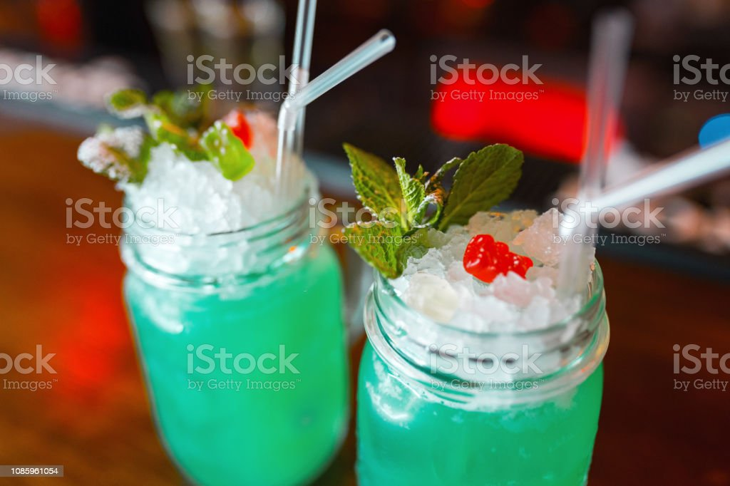 Bright blue delicious alcoholic cocktails 'Blue Lagoon' in a glass with ice cubes with tubes decorated with mint leaves and berries. Weekend and night party at the bar. Close-up. stock photo