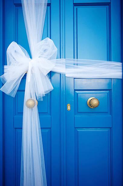 leuchtend blauen türen mit schicken weißer schleife - türbänder stock-fotos und bilder