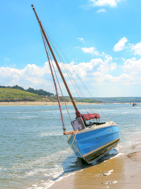 bright blue sail boat beached on sandy shore with small waves - blue sky in summer stock photo