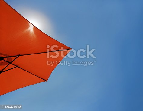 Bright blue sky background with a red beach umbrella. Theme of tourism, relax, vacation, holiday, repose, take a rest by the sea. Website cover template, flat top view, close-up