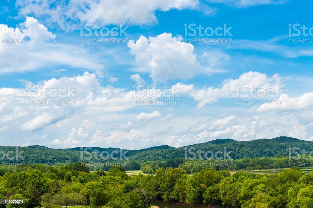 Strahlend blauer Himmel mit Wolken über grünen Wald, natürlichen Hintergrund. – Foto