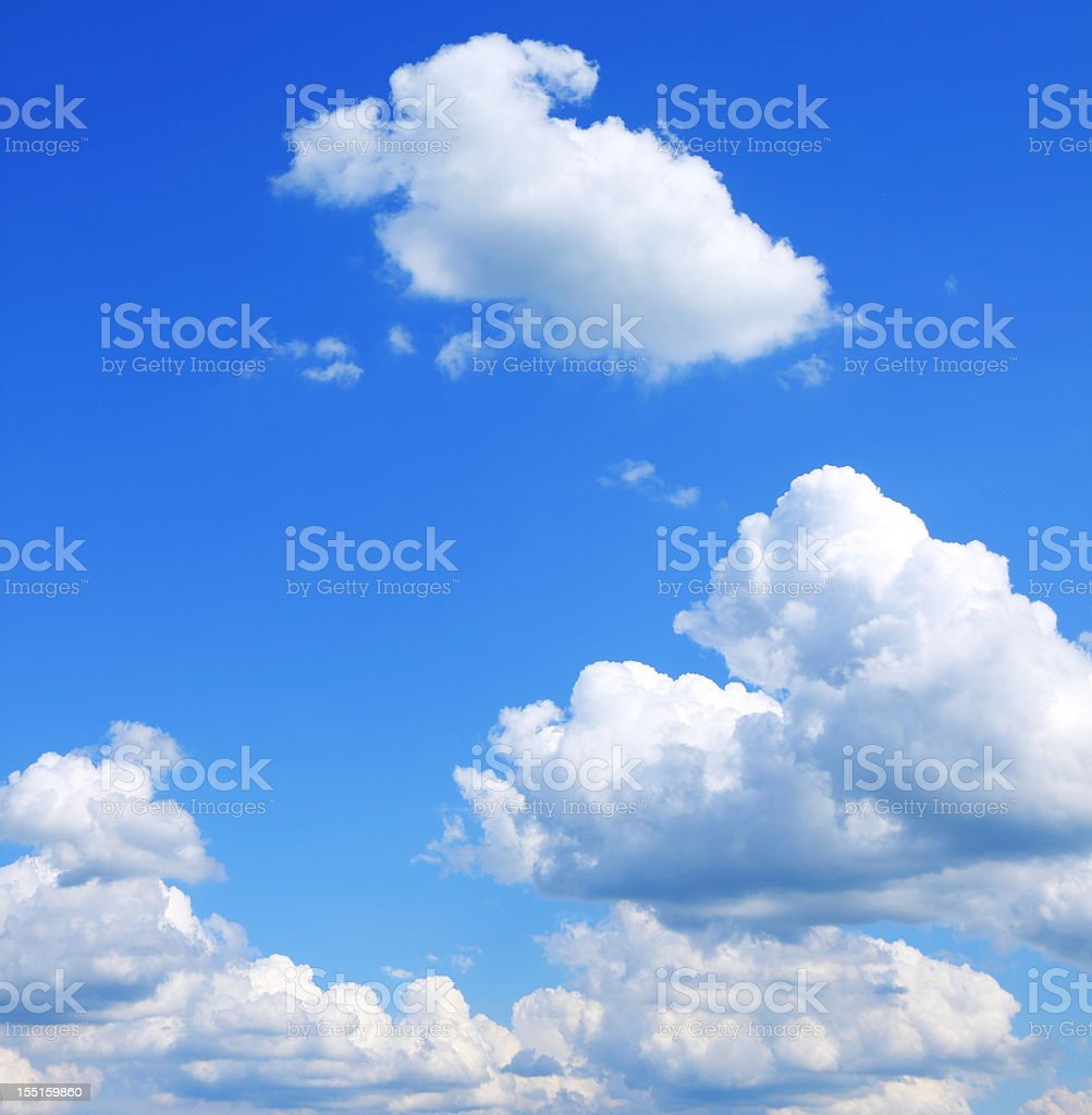 Bright blue sky with puffy clouds stock photo