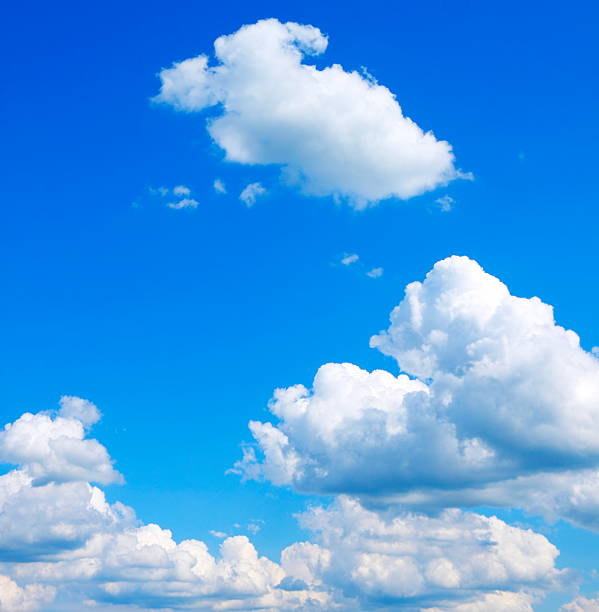 bright blue sky with puffy clouds - cumulus stockfoto's en -beelden