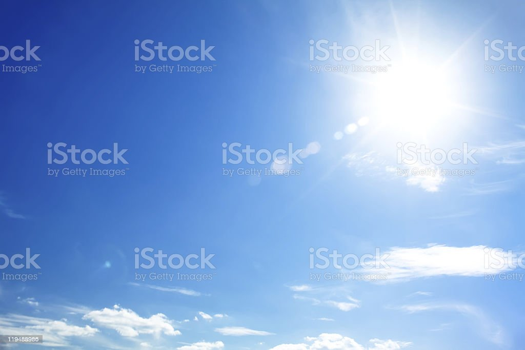 bright blue sky with the sun causing lens flare stock photo