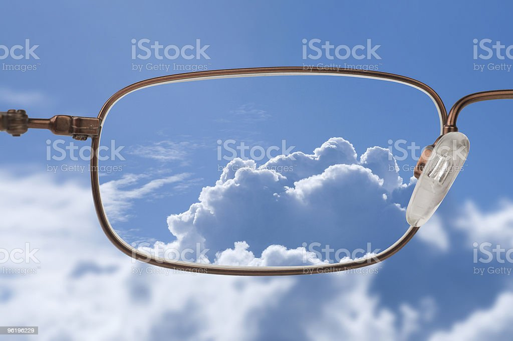 Bright blue sky with white clouds through a glasses lens royalty-free stock photo