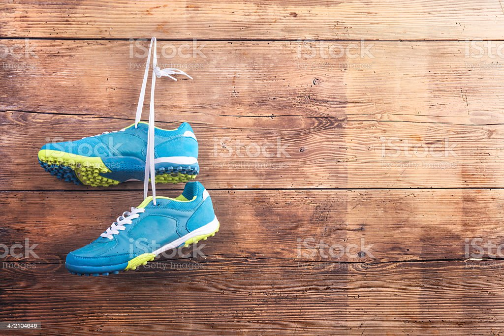 Bright blue sports shoes hanging on a wooden surface stock photo