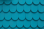 Wooden blue background, very vibrant color. The shingles create a fun rounded pattern.