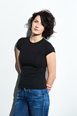 Bright brunette woman in black tshirt and jeans standing by the wall with hands over back