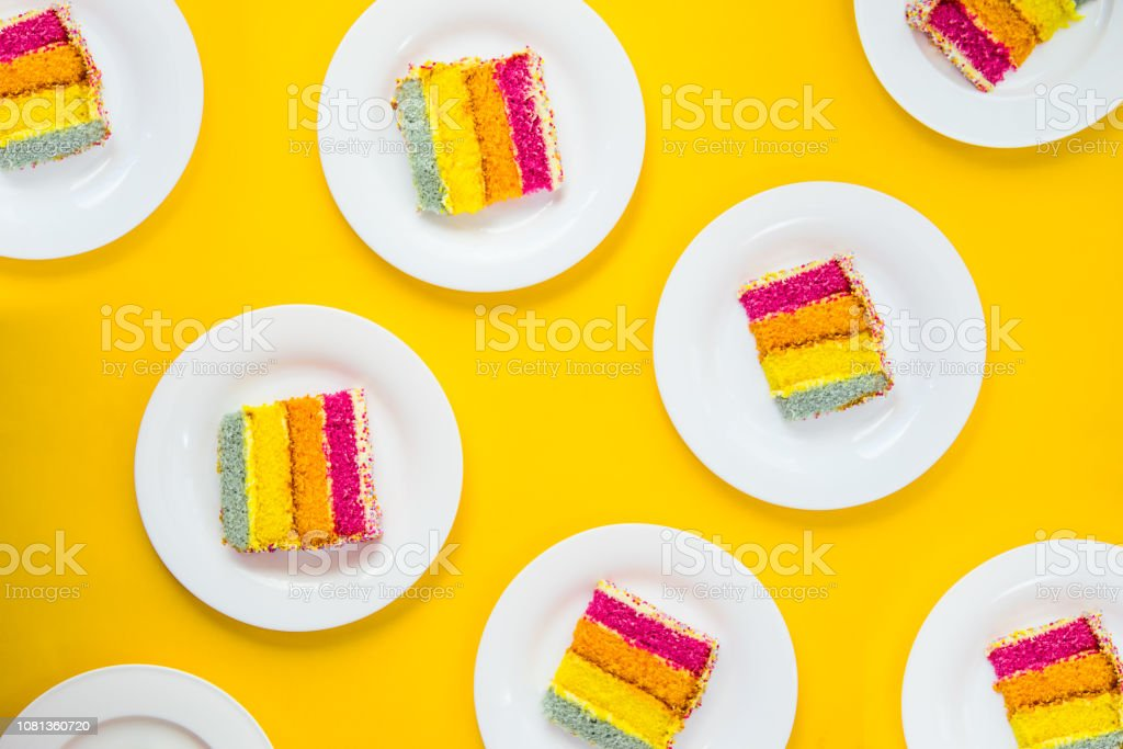 Bright cake pattern. Top view set of rainbow cake slices on white round plates on yellow background. Happy bithday, party layout concept. Selective focus. Copy space. stock photo