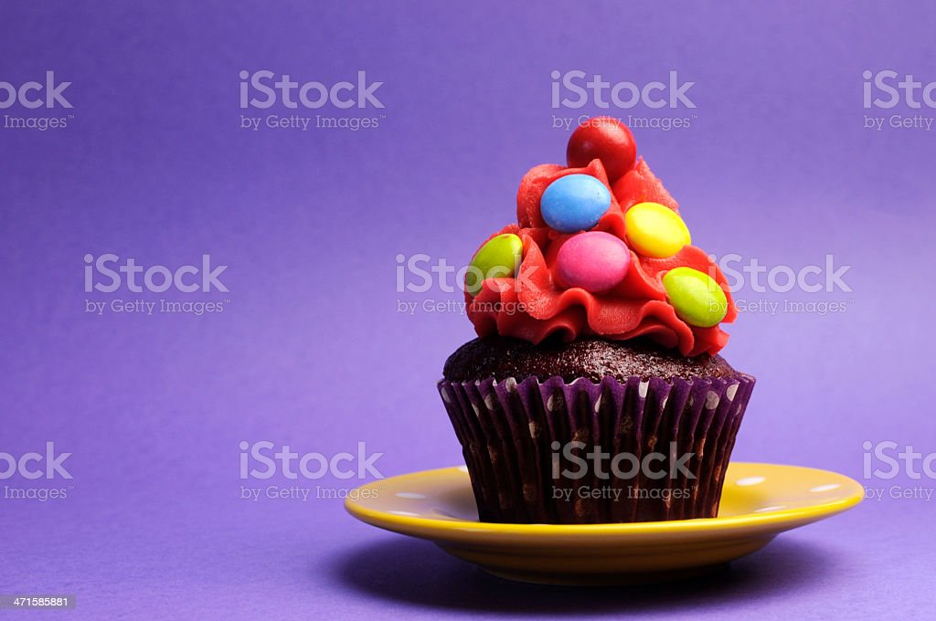 Bright candy covered cupcake on yellow polka dot plate royalty-free stock photo